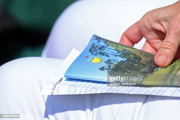 A patron holds a course guide and pair sheet during the first round of the 2015 Masters Tournament at Augusta National Golf Club on April 9 2015 in...