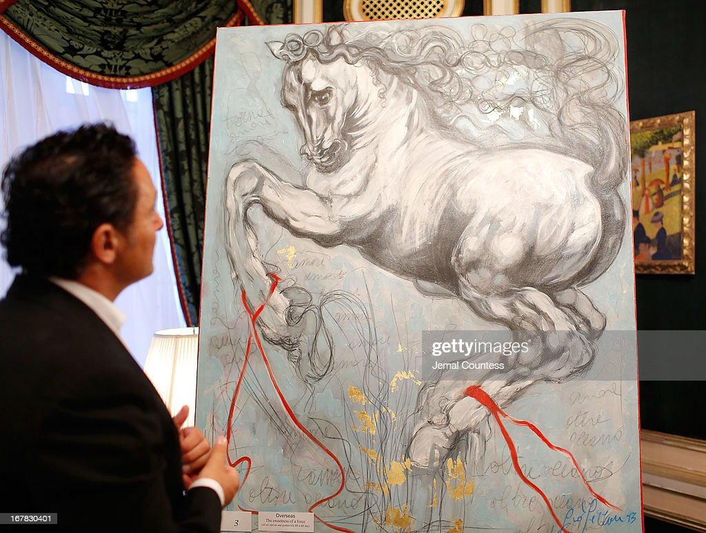 A patron looks at a piece by painter Giovanni Perrone on display during the exhibition of artwork featuring Giovanni Perrone and hosted by Ivana Trump and Mark Antonio Rota on April 30, 2013 in New York City.