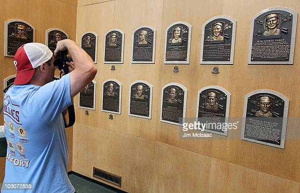 A patron of the Baseball Hall of Fame and Museum takes a photograph of the plaques of inducted members during induction weekend on July 24 2010 in...