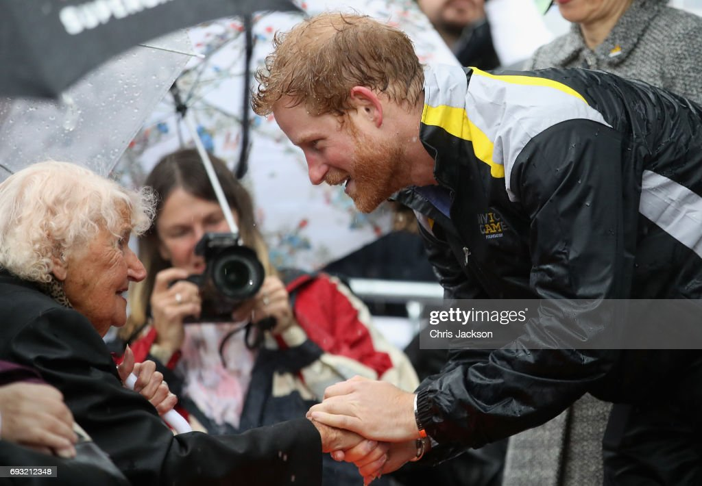 Patron of the Invictus Games Foundation Prince Harry hugs 97 year old Daphne Dunne during a walkabout in the torrential rain ahead of a Sydney 2018 Invictus Games Launch Event at the Overseas Passenger Terminal on June 7, 2017 in Sydney, Australia. Prince Harry is on a two-day visit to Sydney for the launch of the Invictus Games Sydney 2018. The fourth Invictus Games will be held in Sydney from 20th to 27th October, 2018 and will include over 500 competitors from 17 nations competing in 10 adaptive sports events.