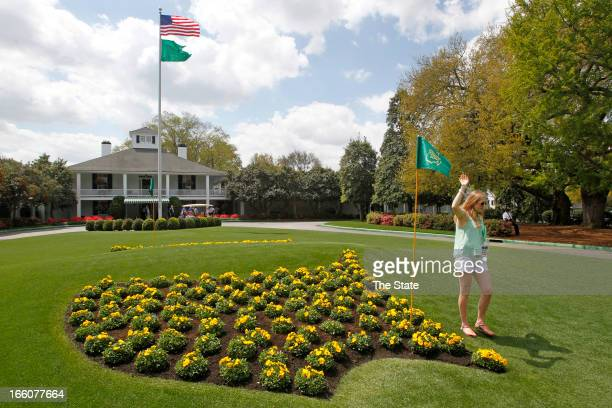 A patron poses for photos next to the Masters logo in flowers at Founders Circle in front of the Augusta National clubhouse in Augusta Georgia during...