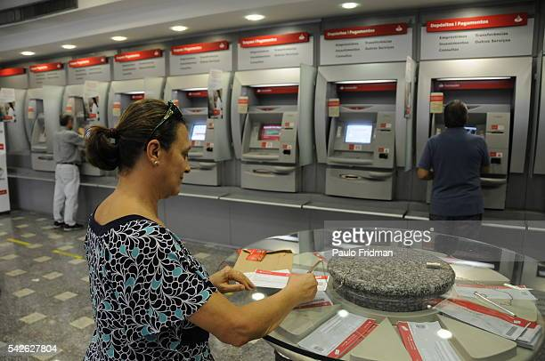 A patron prepares a deposit slip near ATMs at a Banco