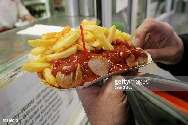 A patron takes his serving of currywurst at Curry 36 one of Berlin's most famous currywurst stands March 17 2006 in Berlin Germany Currywurst...