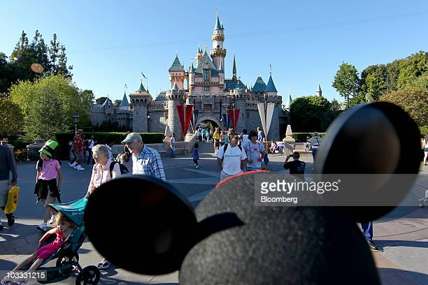 A patron wearing a Mickey Mouse hat walks in front of Sleeping Beauty Castle at Walt Disney Co's Disneyland amusement park in Anaheim California US...
