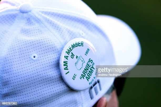 A patron wears a pin that reads 'I am a member of Arnie's Army' in remembrance of Arnold Palmer during the first round of the 2017 Masters Tournament...