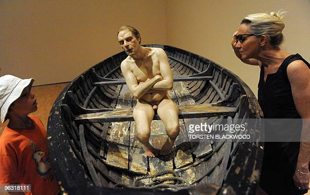 Patrons admire the wood silicon and fibreglass scuplture 'Man in a Boat' by Australian artist Ron Mueck at the National Gallery of Victoria in...