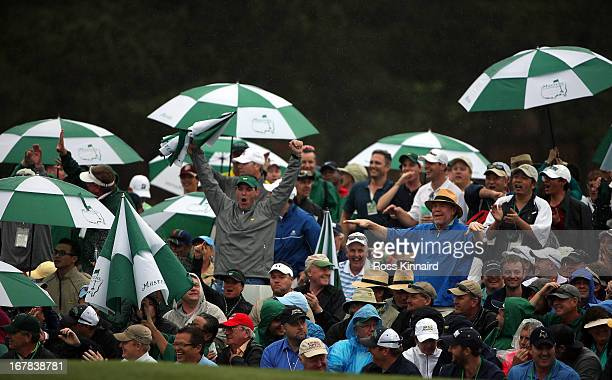 Patrons around the 18th green shelter from the rain during the final round of the 2013 Masters at the Augusta National Golf Club on April 14 2013 in...