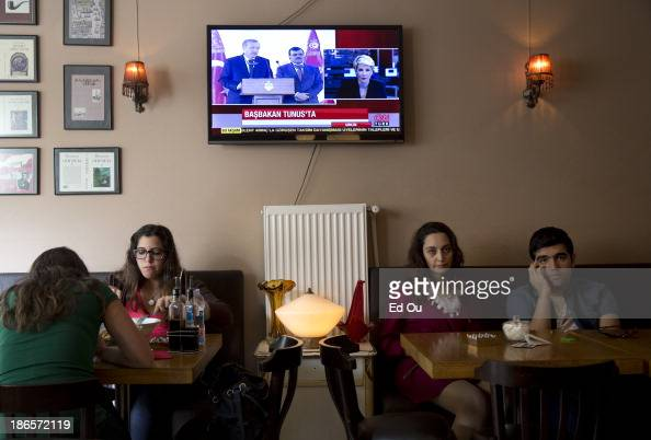 Patrons at an Istanbul Turkey restaurant look on as a television screen shows Turkish Prime Minister Recep Tayyip Erdogan during a joint press...