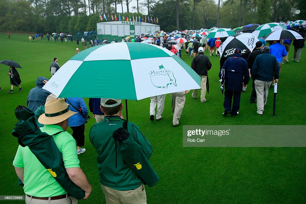 Patrons carrying umbrellas are evacuated from the course after play was suspended due to weather during a practice round prior to the start of the 2014 Masters Tournament at Augusta National Golf Club on April 7, 2014 in Augusta, Georgia.
