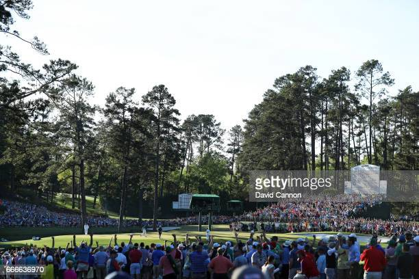 Patrons cheer as Sergio Garcia of Spain celebrates making a putt for eagle on the 15th hole during the final round of the 2017 Masters Tournament at...