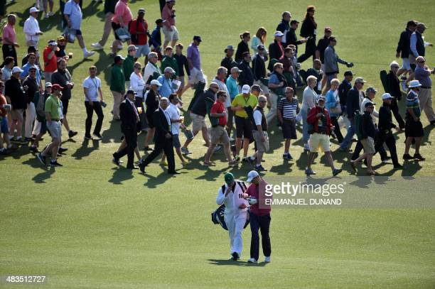 Patrons cross on the fairway at the 1st hole as Justin Rose of England makes his way during a practice round at the 78th Masters Golf Tournament at...