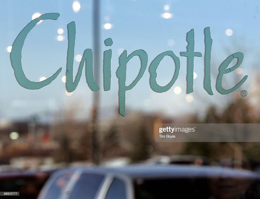 A patron's face, bottom right, is slightly visible beyond signage through a window of a Chipotle restaurant December 2, 2005 in Glenview, Illinois. McDonald's Corp., owners of 92 percent of Chipotle, are preparing its Mexican-style eateries for an initial public offering.
