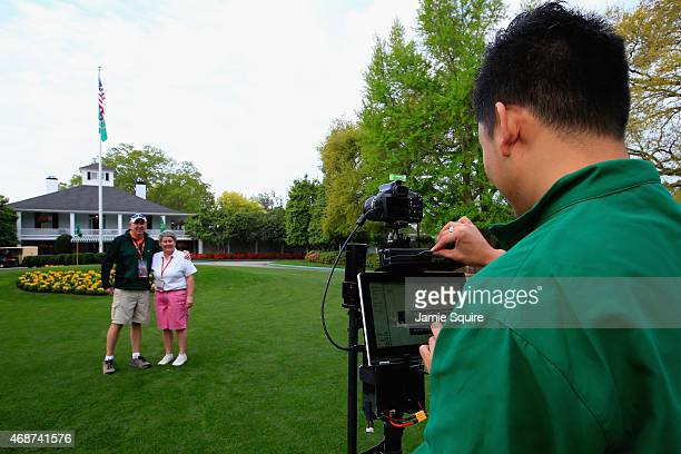 Patrons get their photo taken in front of the club house during a practice round prior to the start of the 2015 Masters Tournament at Augusta...