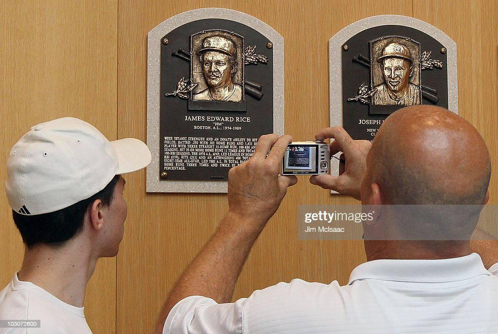 Patrons of the Baseball Hall of Fame and Museum take photographs of the plaques of inducted members during induction weekend on July 24, 2010 in Cooperstown, New York.