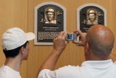 Patrons of the Baseball Hall of Fame and Museum take photographs of the plaques of inducted members during induction weekend on July 24 2010 in...
