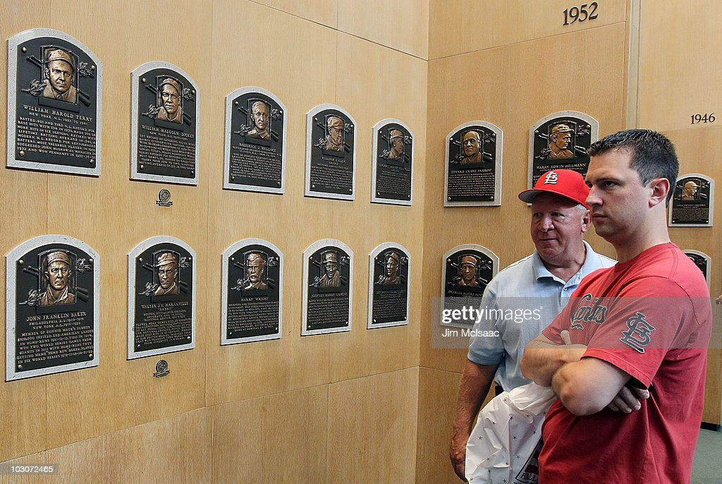 Patrons of the Baseball Hall of Fame and Museum view the plaques of inducted members during induction weekend on July 24 2010 in Cooperstown New York