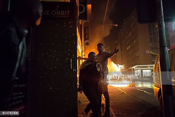Patrons run for safety as a van is on fire in front of the popular jazz bar 'the Orbit' in the Braamfontein district of Johannesburg on October 14...