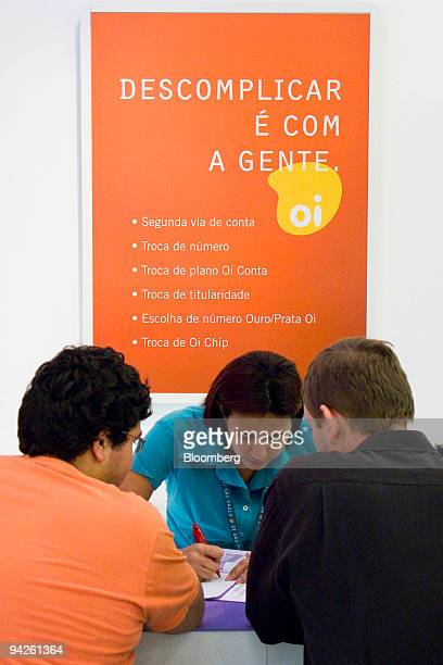 Patrons speak to a representative at an Oi mobile phone store in the Eldorado Mall in Sao Paulo Brazil on Thursday Dec 10 2009 Telemar Norte Leste SA...