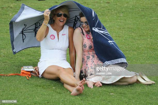 Patrons take cover from the rain under a towel during the final round of THE PLAYERS Championship at the Stadium course at TPC Sawgrass on May 14...