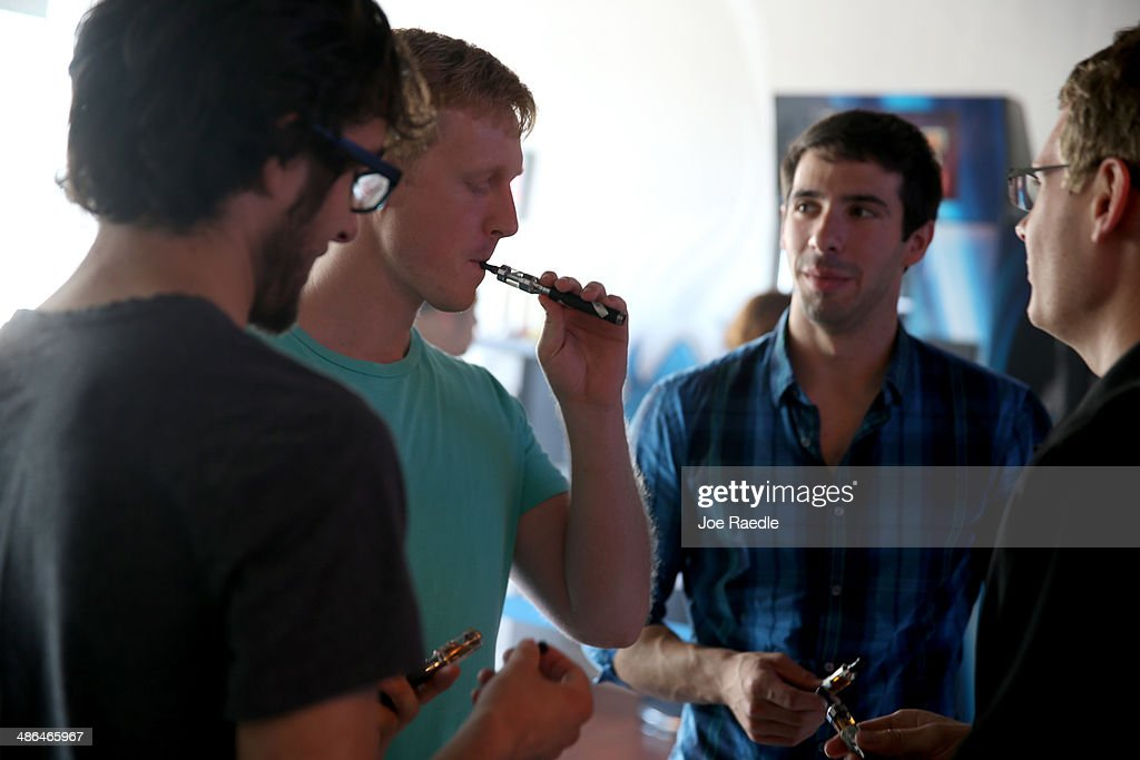 Jon Lusher (2nd L) and Andrew Friedrichs (2nd R) try different flavors of vapor for their electronic cigarettes as they shop at the Vapor Shark store on April 24, 2014 in Miami, Florida. Brandon Leidel, CEO, Director of Operations Vapor Shark, said he welcomes the annoucement by the Food and Drug Administration that they are proposing the first federal regulations on electronic cigarettes, which would ban sales of the popular devices to anyone under 18 and require makers to gain FDA approval for their products.