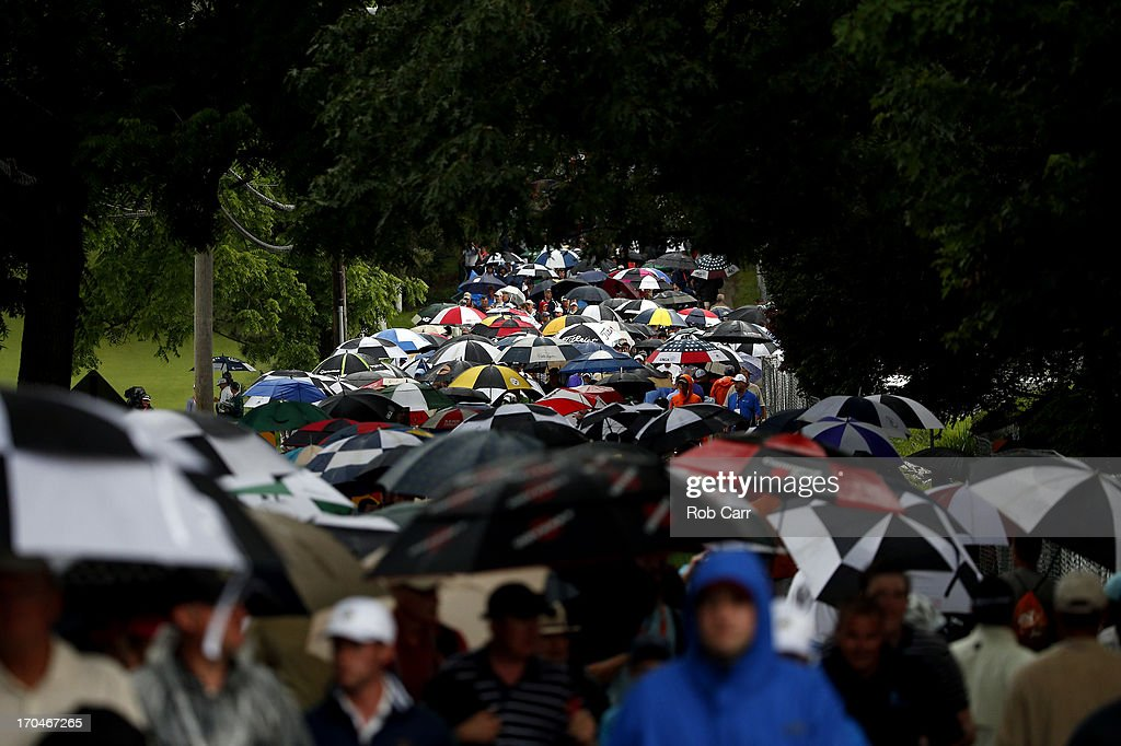 Patrons walk off the course after play was suspended due to weather during Round One of the 113th U.S. Open at Merion Golf Club on June 13, 2013 in Ardmore, Pennsylvania.