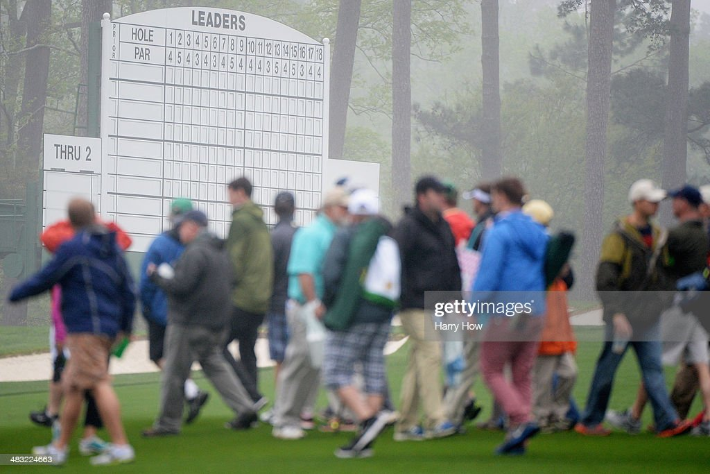 Patrons walk past a leaderboard during a practice round prior to the start of the 2014 Masters Tournament at Augusta National Golf Club on April 7, 2014 in Augusta, Georgia.