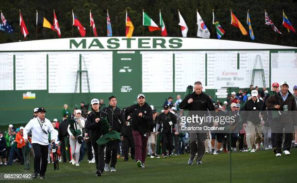 Patrons walk quickly toward the first tee box for the ceremonial opening tee shots by Jack Nicklaus and Gary Player to start The Masters tournament...