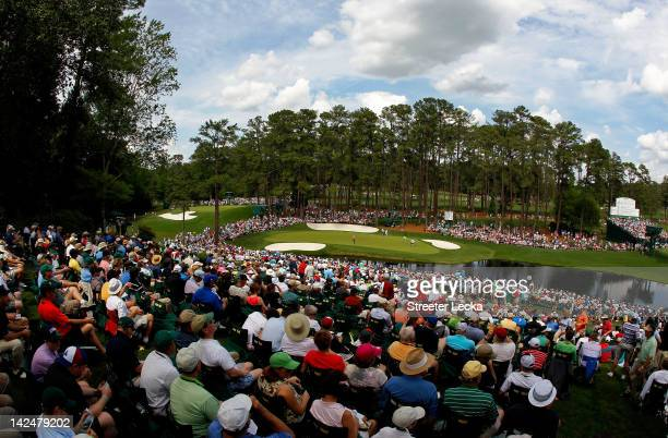 Patrons watch as Henrik Stenson of Sweden Alvaro Quiros of Spain and Gary Woodland of the United States play the 16th green during the first round of...