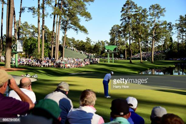 Patrons watch as Rickie Fowler of the United States putts on the 16th green during the third round of the 2017 Masters Tournament at Augusta National...