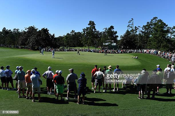 Patrons watch golfers during a practice round prior to the start of the 80th Masters Golf Tournament at the Augusta National Golf Club on April 4 in...