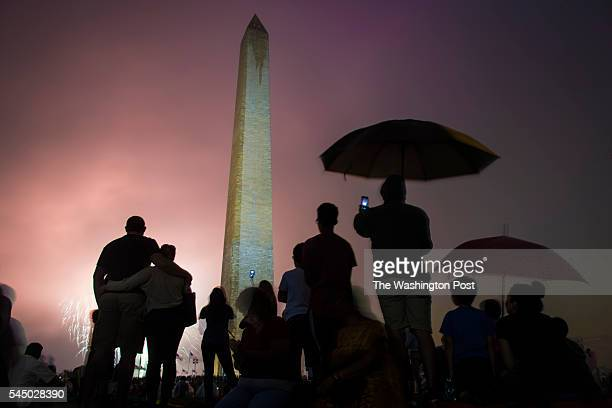 Patrons watch near the Washington Monument as the Independence Day fireworks go off on the National Mall in Washington DC on Monday July 04 2016