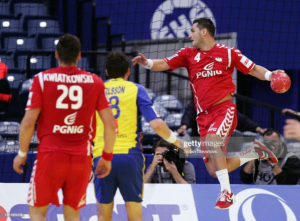 Patryk Kuchczynski (R) of Poland shoots the ball past Tobias Karlsson (L) of Sweden, during the Men's European Handball Championship 2012 main group 1 match between Poland and Sweden, at Belgrade Arena Hall on January 21, 2011 in Belgrade, Serbia.