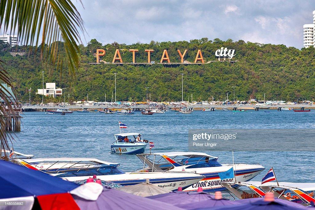 Pattaya city sign, boats and umbrellas on shoreline at Beach Road.