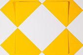 Pattern from yellow envelopes on the white table