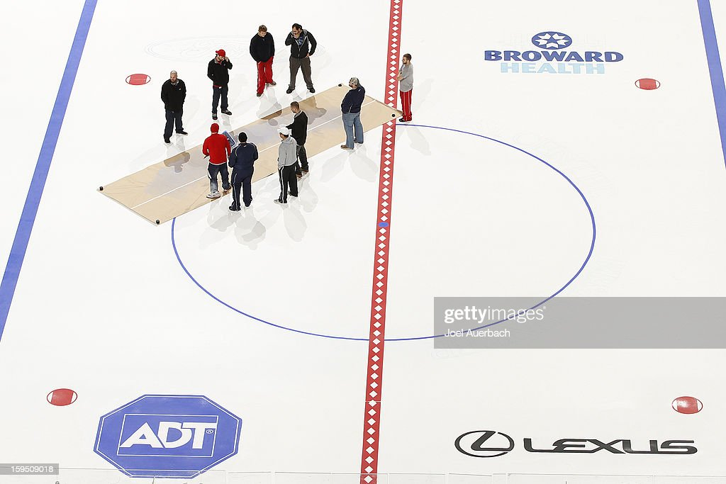 A pattern is placed around the center ice circle with the new name of the arena by members of the Florida Panthers crew before painting the lines and logos at the BB&T Center on January 14, 2013 in Sunrise, Florida.