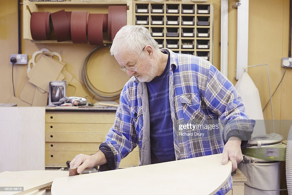 Pattern maker sanding wood in workshop : Stock Photo