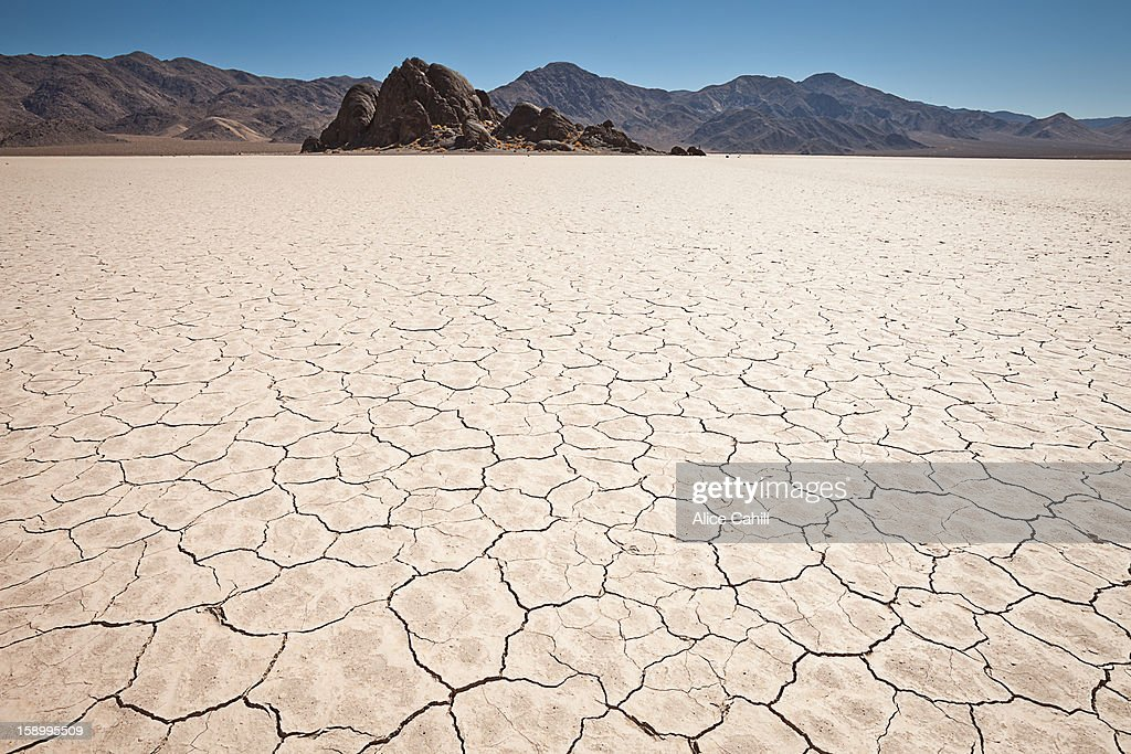Pattern of dry mud on lakebed, distant mountians.