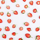 Colorful pattern of strawberry halves on a white background. Top view with copyspace