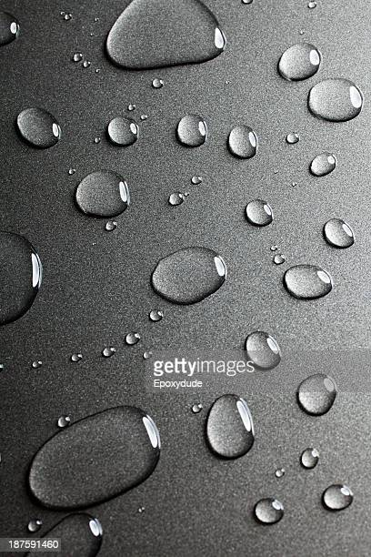 A pattern of various shaped water drops on a nonstick baking sheet