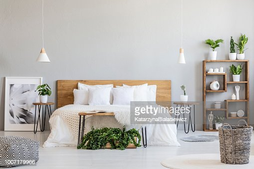Patterned pouf and basket in bright bedroom interior with lamps, plants and poster next to bed. Real photo : Stock Photo