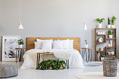 Patterned pouf and basket in bright bedroom interior with lamps, plants and poster next to bed. Real photo