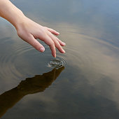 Cropped shot of a finger touching water to form ripples