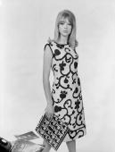 Patti Boyd models a Brilkie sleeveless sheath dress with a large stylised floral pattern She is holding the Beatles album 'A Hard Day's Night'