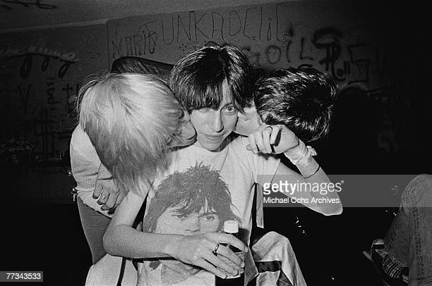 Patti Smith gets a kiss from Iggy Pop and James Williamson of The Stooges in November 1974 backstage at the Whisky a Go Go in Los Angeles California