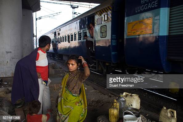 PattiDas and his wife Leela get dressed piece of waste ground beneath a flyover near Okhla station as a train passes and a passenger shouts abuse at...
