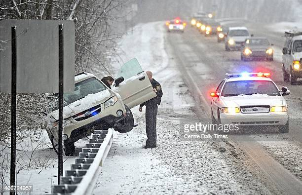A Patton Township police officer helps a woman out of her vehicle after she slid off N Atherton Street and was stranded on top of a guard rail in...