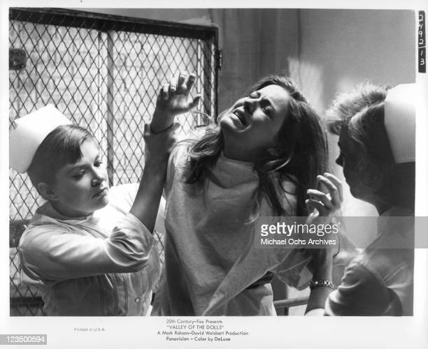 Patty Duke being restrained by nurses in a scene from the film 'Valley Of The Dolls' 1967
