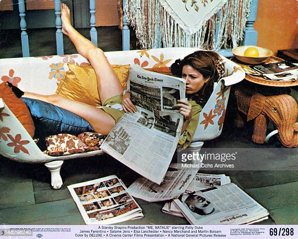 Patty Duke laying down reading the newspaper in a scene from the film 'Me Natalie' 1969