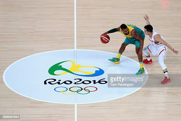 Patty Mills of Australia dribbles the ball against Jiwei Zhao of China during the Men's Basketball Preliminary Round Group A China vs Australia on...