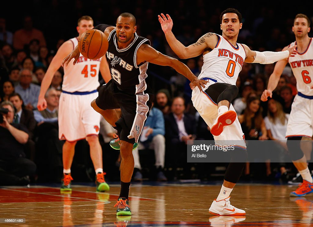 Patty Mills of the San Antonio Spurs and Shane Larkin of the New York Knicks reach for the ball during their game at Madison Square Garden on March...